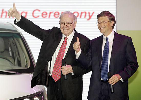 Billionaire financier and Berkshire Hathaway Chief Executive Warren Buffett (L) and Microsoft founder Bill Gates gesture at the national launch ceremony for the BYD M6 vehicle in Beijing