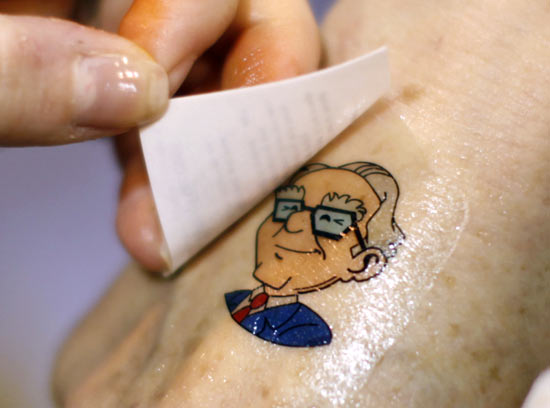 A Berkshire Hathaway shareholder has a temporary tattoo of BH Chairman Warren Buffett applied to her hand at the company trade show during the BH annual meeting in Omaha, Nebraska