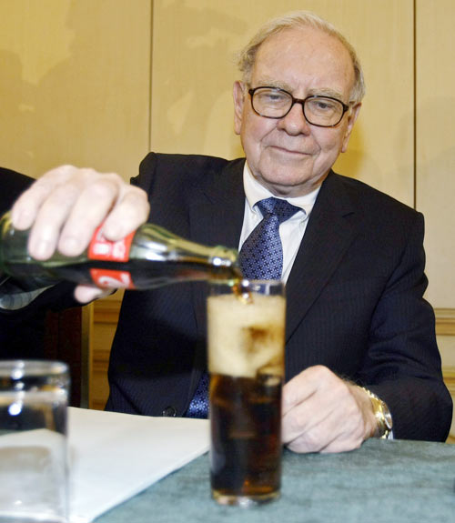 US Investor Warren Buffett fills a glass with Coke during a news conference in Madrid