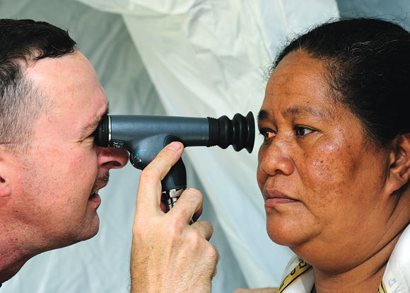 An optometrist uses an ophthalmoscope to check the retina of a patient