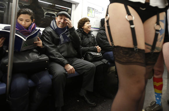 People watch as participants in the No Pants Subway Ride take the 6 train downtown in New York January 13, 2013