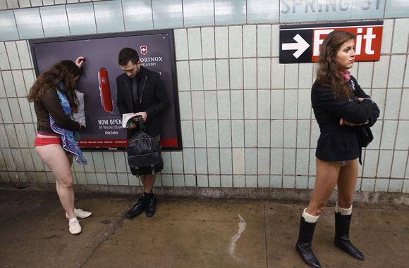 People taking part in the No Pants Subway Ride wait to board the uptown 6 train in New York January 13, 2013