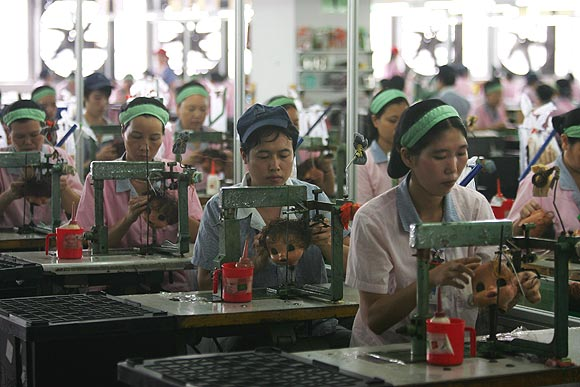 Workers assemble dolls at the production line of Jetta (China) Industries Co., Ltd.