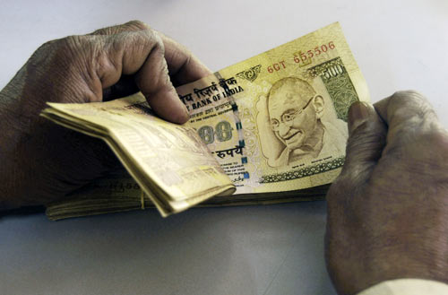 A bank employee counts currency notes at a cash counter inside a bank