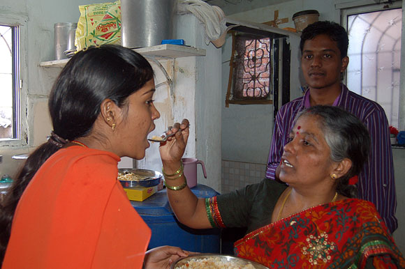 Prema Jayakumar's mother Lingammal feeds her as her brother Dhanraj savours the moment.