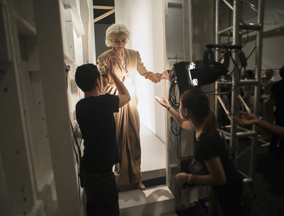 Model Carmen Dell'Orefice (C) is helped off the runway backstage after participating in the runway show for fashion designer Norisol Ferrari's Spring/Summer 2013 collection during New York Fashion Week September 10, 2012. The collection is Ferrari's first runway show.