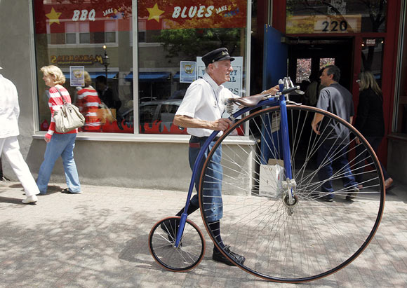 A man walks an old fashioned bicycle down the street at the Watch City Festival celebrating Steampunk in Waltham, Massachusetts May 13, 2012. Steampunk is a movement that explores the notion of what the world might look like had modern technology been available at the turn of the twentieth century.