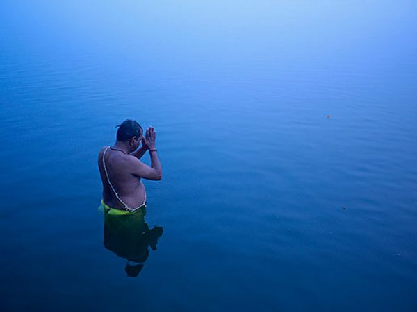 Hindu devotee stands in the waters of river Ganges to offer prayers to Sun god at dawn in Varanasi.