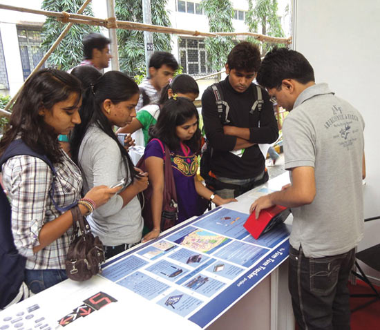 An engineer explains the Tum Tum Tracker app's features to students