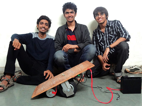 The self balancing skateboard's founders pose with their innovation