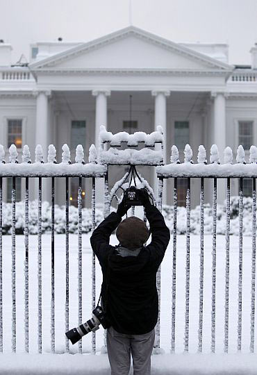 A photojournalist takes pictures of the White House in Washington, DC
