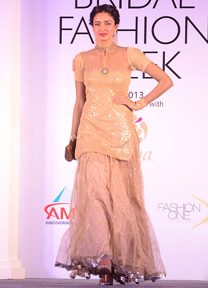 Dayana Erappa walks the ramp for Rina Dhaka at the Aamby Valley India Bridal Fashion Week Preview in Delhi on July 10, 2013