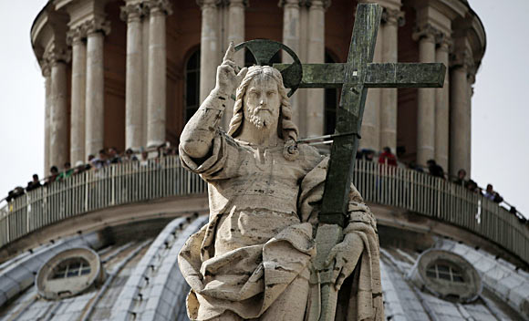The statue of the Christ is seen in front of the dome of Saint Peter's Basilica at the Vatican.