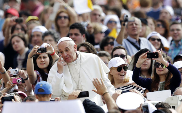 Pope Francis gestures as he arrives to lead his Wednesday general audience in Saint Peter's Square at the Vatican June 5, 2013.