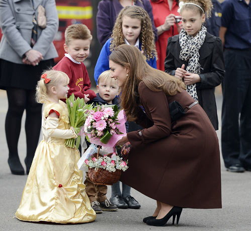 Britain's Catherine, Duchess of Cambridge receives flowers from children during a visit to Peak Lane fire station in Grimsby, northern England March 5, 2013.