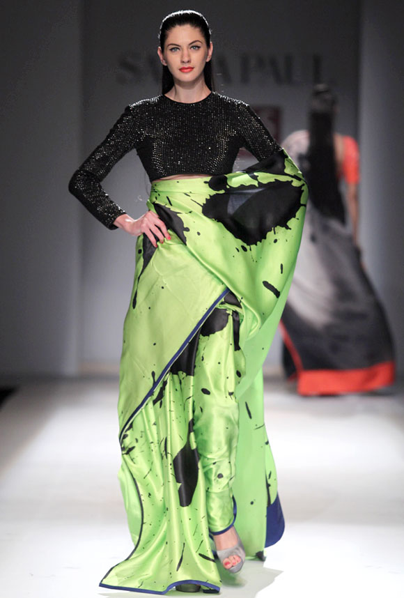 A model sports an ink blot black and green saree with a short black embellished blouse.