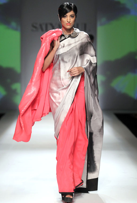 Jesse Randhawa shows a pink, white and grey saree, with a collared blouse and a long embellished jacket.