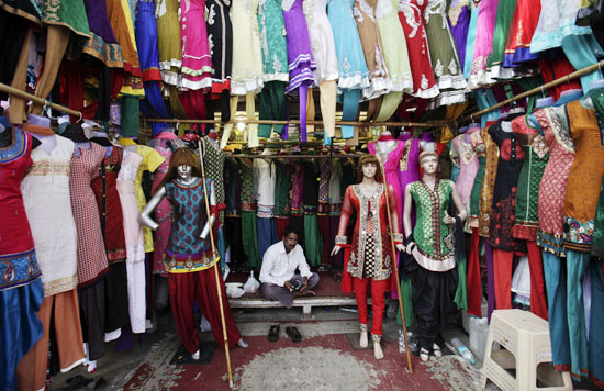 A vendor waits for customers at his shop selling clothes, at a market in Mumbai January 31, 2012. India's economy is expected to grow faster in the next fiscal year than the pace it is expected to expand in the current year, Kaushik Basu, the chief economic adviser to the finance ministry, said on Tuesday.