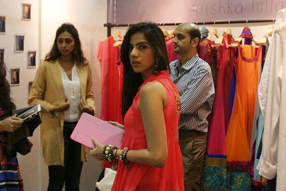 Fashion designer Nishka Lulla inside her stall speaking with interacting buyers