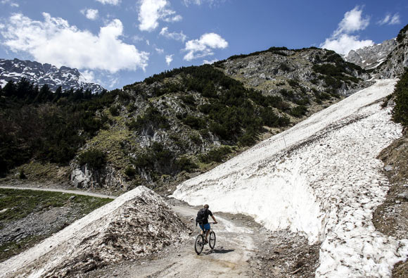 A cyclist rides past remnants of a recent winter avalanche, on a sunny spring day in the western Austrian city of Innsbruck.