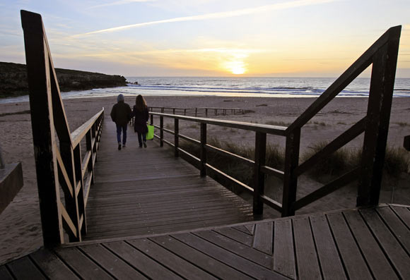A couple walks to the beach during sunset at Lisandro beach on the Atlantic sea coast of Portugal, 40 km north of Lisbon.