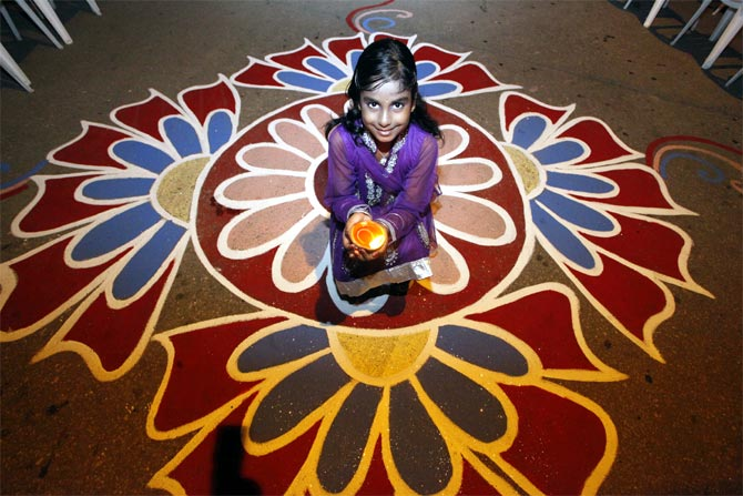 A young lady holds a diya, or oil lamp, in a street during Diwali celebrations.