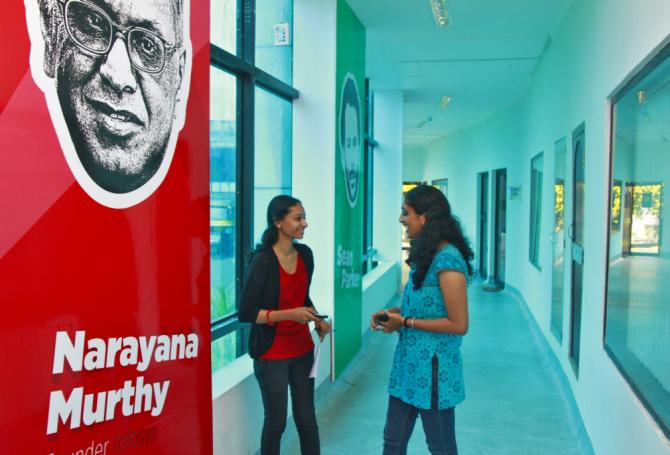 Employees talk as they stand next to flex board poster of Infosys founder Narayana Murthy at the Start-up Village in Kinfra High Tech Park in the southern Indian city of Kochi