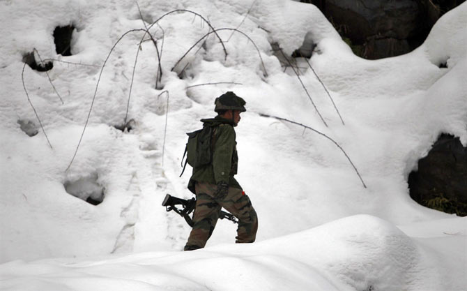 An Indian army soldier patrols near the Line of Control in Churunda village, about 129 km (80 miles) northwest of Srinagar