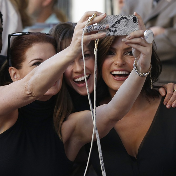 Actress Debra Messing uses her mobile phone to take a picture with actors Hilary Swank (C) and Mariska Hargitay. Picture used here for representational purposes only.