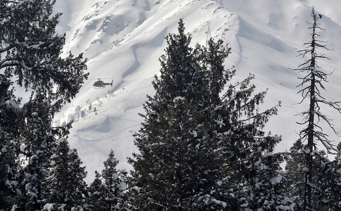 A helicopter carrying heli-skiers flies behind snow-covered trees in Gulmarg, 55 km west of Srinagar.