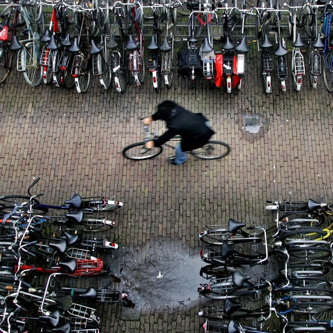 A man rides his bike in a bicycle shed near Central Station Amsterdam. There are more bicycles than people in the Netherlands, where each resident clocks up an average of 917 km (573 miles) a year on two wheels.