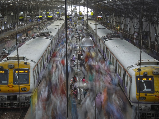 Commuters disembark from crowded suburban trains during the morning rush hour at Churchgate railway station on World Population Day in Mumbai.