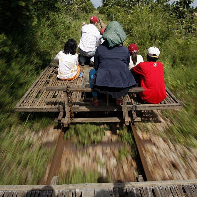 Cambodians ride a bamboo train, known locally as a norry, at new village train station in Pusat province 200 km northwest of Phnom Penh.