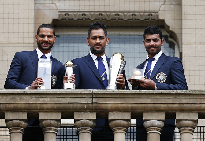 India's cricket players Shikhar Dhawan (L), Mahendra Singh Dhoni (C) and Ravindra Jadeja pose with the ICC Champions Trophy on the balcony of the City Council building in Birmingham, central England, June 24, 2013.