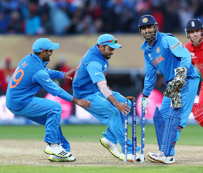 James Tredwell (R) of England cuts a lonely figure as India players Dinesh Karthik (L) Suresh Raina (2L) and MS Dhoni (2R) celebrate their 5 run victory during the ICC Champions Trophy Final match between England and India at Edgbaston on June 23, 2013 in Birmingham, England.