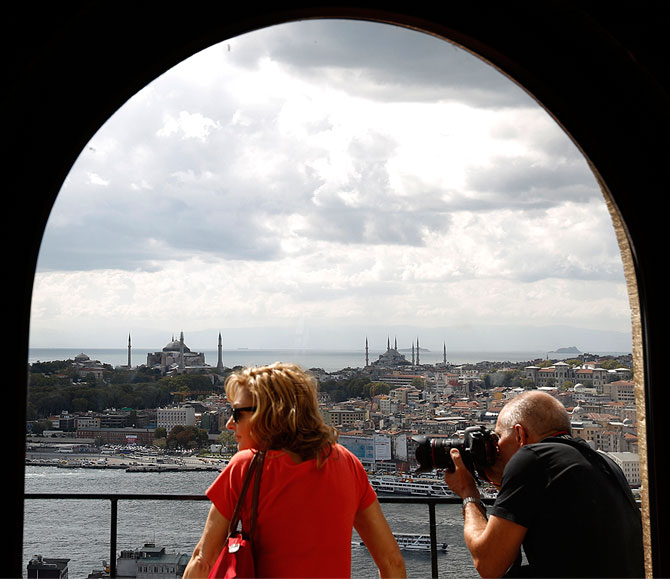 ourists, with the Hagia Sophia museum (L) and Blue Mosque (R) in the background, look at the old city from the historical Galata Tower in Istanbul