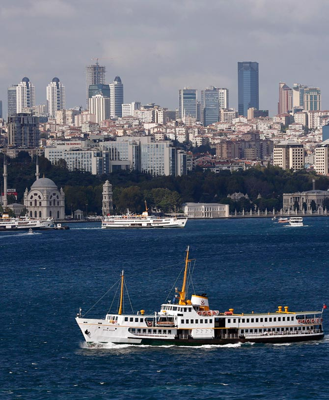A ferryboat moves along the Bosphorus and past the city's skyscrapers (rear) in Istanbul