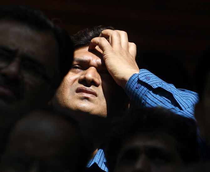A man looks at a large screen displaying India's benchmark share index on the facade of the Bombay Stock Exchange (BSE) building in Mumbai March 13, 2008. Indian shares fell nearly 5 percent by Thursday afternoon to their lowest in more than six months, led lower by index heavyweights Reliance Industries Ltd.