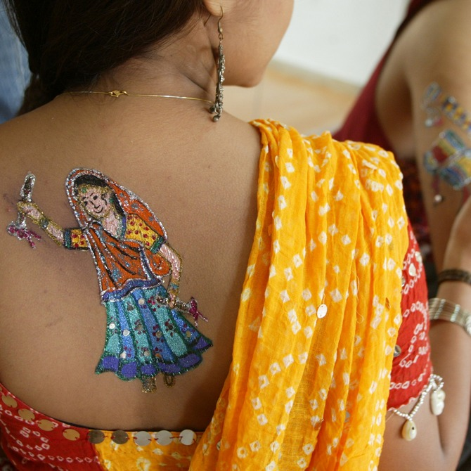 An Indian model (L) has a picture of a traditional Garba dancer painted on her back, as another gets hers painted.