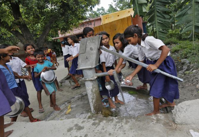 Schoolchildren wash their plates before having their mid-day meal at a primary school in Brahimpur village, Chhapra, Bihar, July 19, 2013.