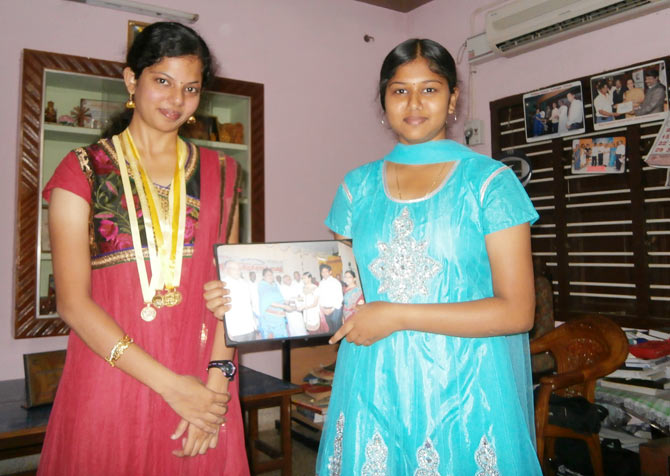 S Alagu with her sister Anandi showing a picture of the latter receiving a citation from the Tirunelveli mayor for scoring 99 per cent in Prathmic Hindi