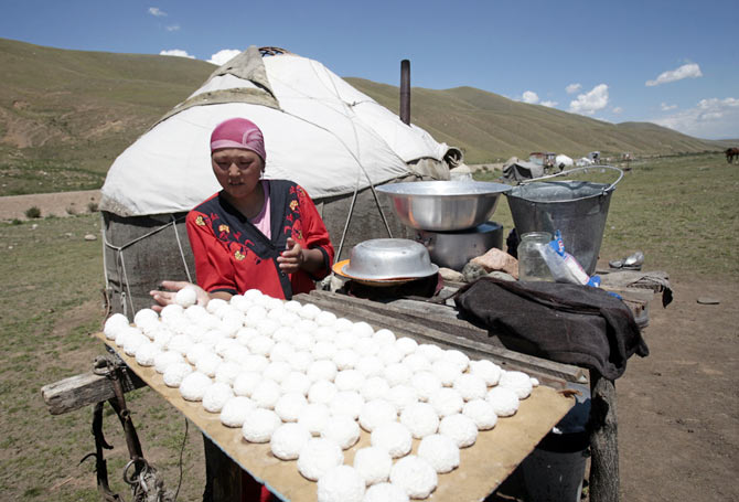 A woman forms balls of salted cow cheese to dry in the sun in the Susamyr Valley near the Bishkek-Osh highway, some 200 km from Bishkek. The Bishkek-Osh highway is part of the historic Silk Road, an ancient trade route running through various regions of the Asian continent into China.