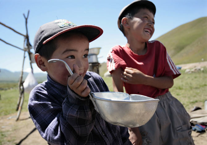A boy drinks from a ladle in the Susamyr Valley near the Bishkek-Osh highway.