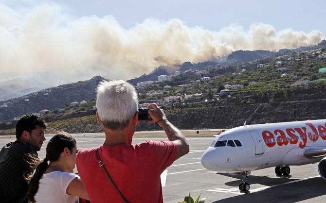 Tourists take photos of forest and bush fires on the mountains on the Portuguese island of Madeira island while waiting for the local airport to re-open July 19, 2012.