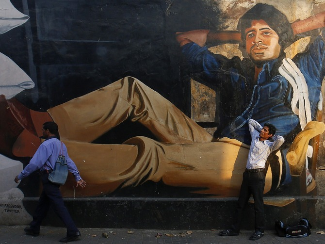 Ram Pratap Verma, a 32-year-old aspiring Bollywood film actor, poses in front of a mural of actor Amitabh Bachchan in Mumbai May 1, 2013. Bollywood is an addiction for many; an addiction that attracts thousands of aspiring stars to the city of Mumbai. Ram Pratap Verma made the journey from his small village eight years ago, and despite carrying his whole 'home' inside his bag, he is determined not to give up on his ambitions.