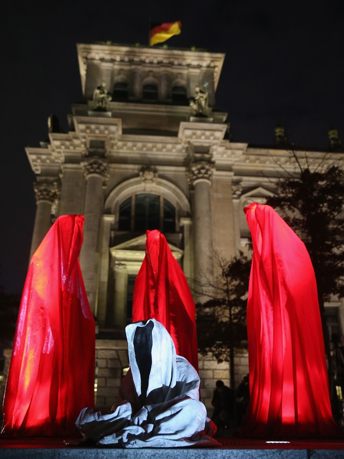 Illuminated sculptures of cloaked figures in red surround one that is seated outside the Reichstag as part of the Festival of Lights on October 14, 2013 in Berlin, Germany. Landmarks across the city are illuminated in colors and patterns in the annual Festival of Lights that always takes place in October.