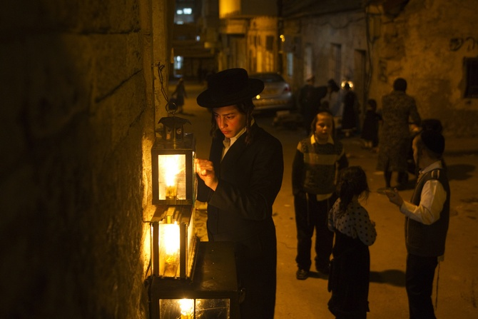 An Ultra-Orthodox Jewish man lights candles for the holiday of Hanukkah in Jerusalem's Mea Shearim neighbourhood.