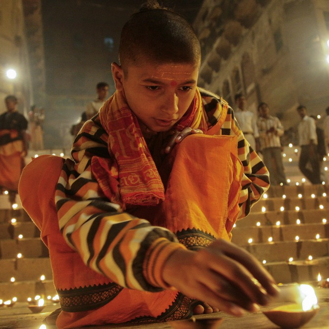 A Hindu devotee lights an earthen lamp on the steps of Sindhiya Ghat, Varanasi.