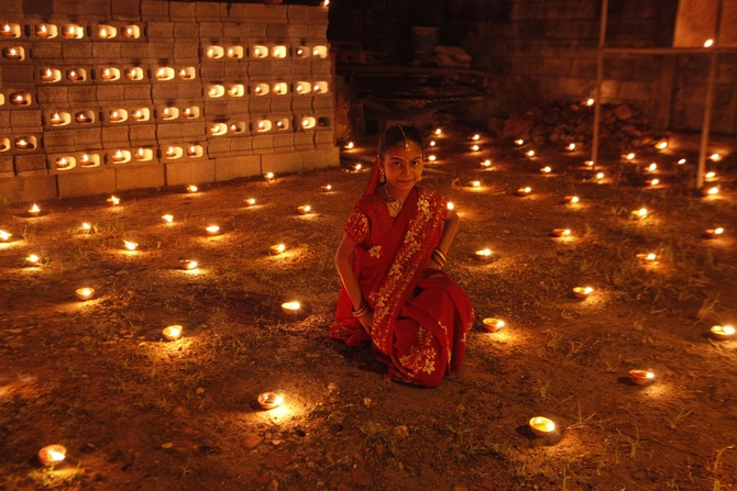 A girl sits among diyas, or oil lamps, in her yard during Diwali celebrations in Felicity, central Trinidad.