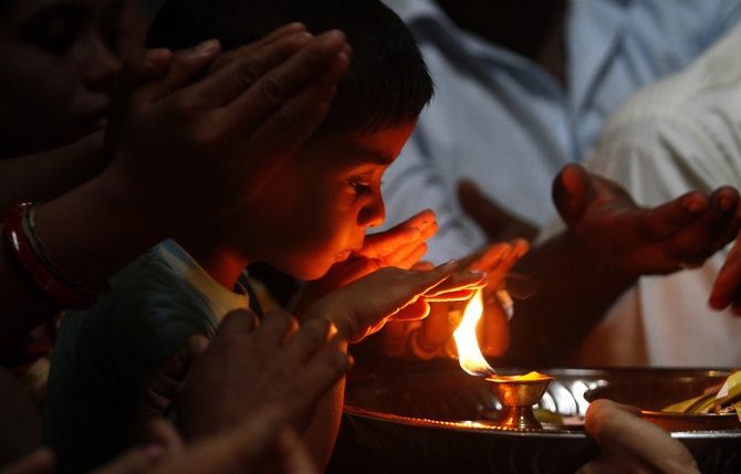 A Hindu boy prays during the festival of Diwali at Shivm Kovi temple in Colombo